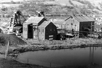 Coegnant Colliery just before it closed in 1981. The pond in the foreground is the 'feeder' for the boliers. An almost unique feature of this colliery was that the head frame was encased in concrete.